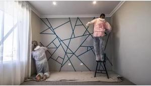 Ze bedekken de muur met stukken kleefband. Als ze klaar zijn met het schilderen,