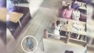 Ze aten in een restaurant en hun kleine zoon speelde twee bankjes achter hen. Al