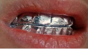 Plaats aluminiumfolie op je tanden en wacht een uur. De resultaten zullen je ver
