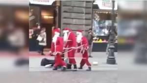 Drie Kerstmannen dansen op straat. Wanneer voorbijgangers dichterbij komen, gelo