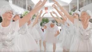 Negen in het wit geklede 82-jarige vrouwen dansen en zingen. Kijk naar die oma\'
