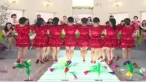 Vrouwen in rode jurken staan in één lijn. Wat ze even later doen, maakt dat iede